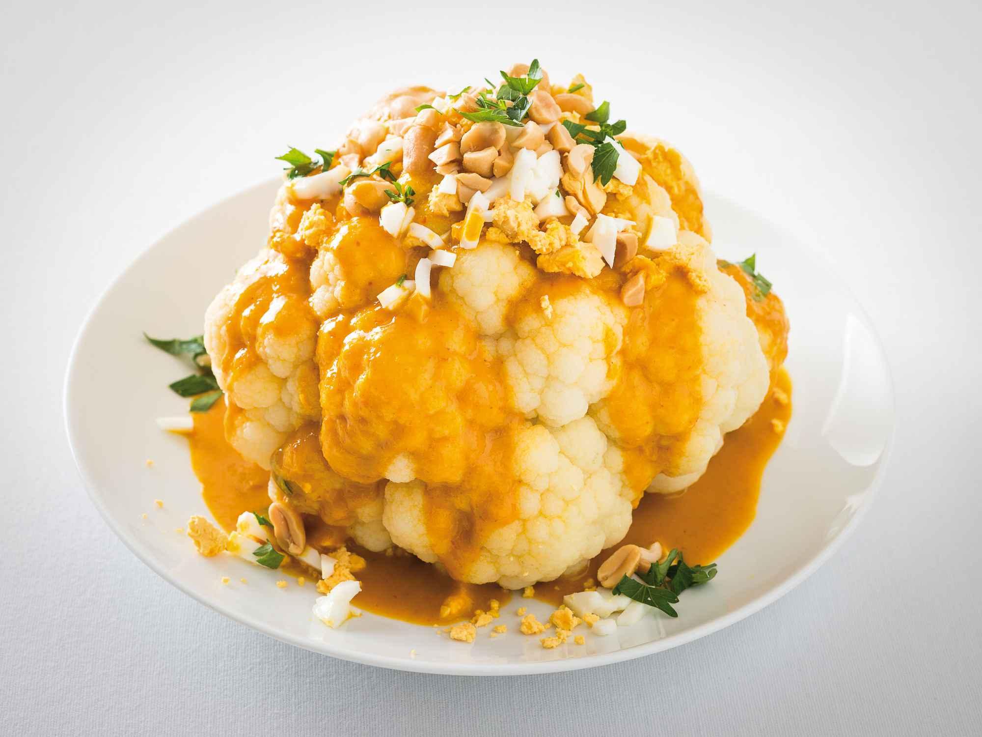 Ganzer Blumenkohl mit Kokosmilch-Currysauce, gehacktem Ei und Erdnüssen