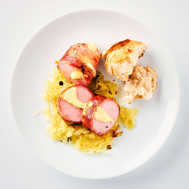 Fleischwurst im Speckmantel auf Weinsauerkraut
